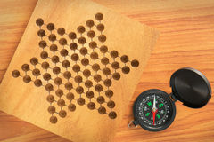 Black compass with star pattern on wooden plate Stock Images