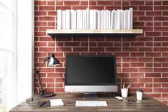 Black computer monitor against brick wall. Black computer monitor is standing on a dark wooden desk near a brick wall. There is a bookshelf above it and a window Stock Photos