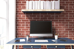 Black computer monitor, blue desk. Black computer monitor is standing on a blue desk near a brick wall. There is a bookshelf above it and a window on the left Stock Photo