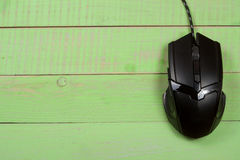Black computer mouse on a green wooden background with copy space for your text. Top view Royalty Free Stock Image