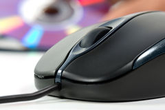Black computer mouse and optical data disc in back Stock Photography