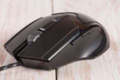 Black computer mouse on a white wooden background close-up Stock Photography