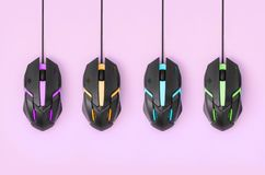 Black computer mouses hang on pastel pink background. Several computer mice hang on a pastel pink background. The concept of cooperative computer video games royalty free stock photos