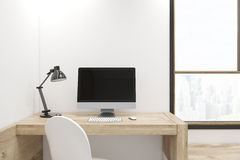 Black computer screen on wooden desk. Black computer screen is standing on a wooden desk in an office with white walls and a large window. 3d rendering, mock up Stock Image