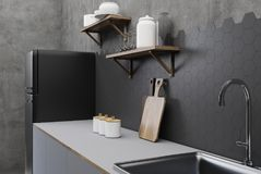 Black and concrete kitchen corner. Black and concrete kitchen interior with hexagon tiles, a countertop with shelves and cutting board and a black fridge in the Stock Image