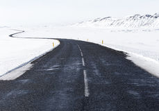 Black Concrete Road in the Middle of White Snow Stock Photo