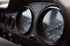 A black control panel in an old car. With speedometer and tachometer stock image