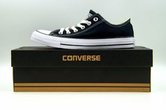 Black Converse All Star low top. Amsterdam, Netherlands - January 16, 2018: Black Chuck Taylor Converse All Star low top standing on a retail box, against a Stock Image