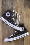 Black Converse sneakers shoes on wood royalty free stock photos