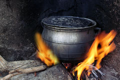 Black coocking pot heated on fire. Boiling water in sooty pot on wood fire with black background, Paga, Ghana Stock Photography