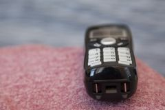 Quiet cordless telephone. A black cordless phone sits waiting to be picked up or dialed royalty free stock photography