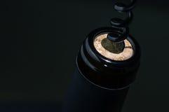 Black corkscrew opens wine. Bottle Stock Photo