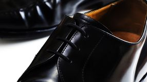 Black Corporate Shoes in macro shot. Macro shoot of highly polished black leather shoes on white surface Royalty Free Stock Photo