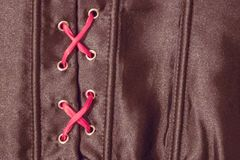Black corset on lacing. The red satin ribbon is tucked into a black corset. Prohibition, a mystery related to sex, passion. Artificial lighting Royalty Free Stock Image