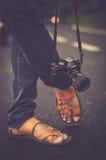 Black Cosina Slr Camera Hanging Beside Foot during Daytime Royalty Free Stock Photography