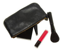 Black cosmetic bag and various makeup products on white background with soft shadows Stock Images