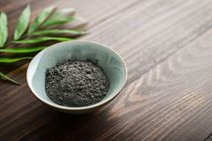 Black cosmetic clay. In coconut bowl on wooden background closeup Stock Image