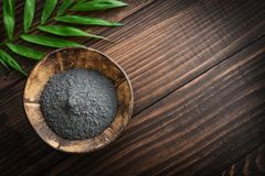 Black cosmetic clay in coconut bowl. On wooden background closeup Stock Photography