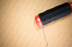 Black cotton sprocket. Black cotton thread on a sprocket, light brown background Stock Photo