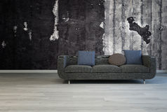 Black couch against grunge dark concrete wall Stock Images
