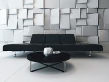 Black couch in front of white ornamental wall Stock Images
