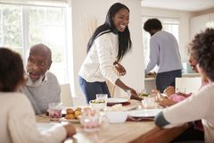 Black couple bringing food to the table for Sunday family dinner for the kids and grandparents royalty free stock photo