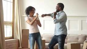 Black couple celebrating moving at new home dancing feels happy