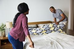 Black couple changing bed sheet together Royalty Free Stock Photography