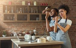 Black couple dancing and singing while baking in kitchen Stock Image