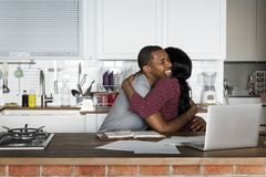 Black couple hugging together while working on laptop royalty free stock photo