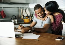 Black couple hugging together while working on laptop stock photography