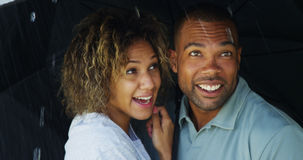 Black couple laughing under umbrella together Royalty Free Stock Images