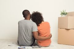 Black couple looking up, sitting on floor. African-american family couple looking up, sitting on floor in new apartment with moving boxes, dreaming about future Stock Images