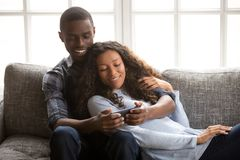 Black couple in love on couch using mobile phone stock photography