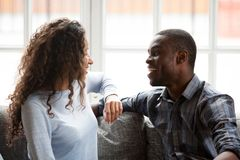 Black couple in love talking sitting on couch at home stock photography