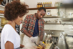 Black couple prepare food behind counter at a sandwich bar Royalty Free Stock Photography