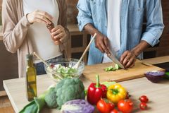 Black couple preparing healthy vegetable salad in kitchen Royalty Free Stock Photography
