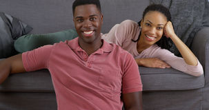 Black couple relaxing on couch and smiling at camera Royalty Free Stock Photos