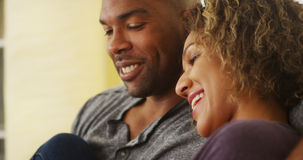 Black couple sitting on couch smiling Royalty Free Stock Photo