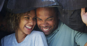 Black couple standing under coat trying not to get wet Stock Photo