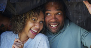 Black couple standing under coat trying not to get wet royalty free stock photography