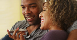 Black couple talking on smartphone Stock Images