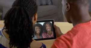 Black couple talking to friends over tablet computer video chat. Young black couple talking to friends over tablet computer video chat Royalty Free Stock Images