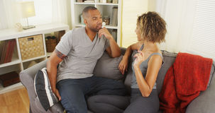 Black couple talking together on couch Royalty Free Stock Photos