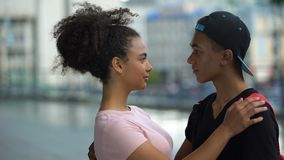 Black couple of teenagers hugging during outdoor date, love connection affection