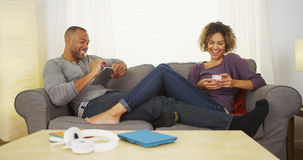 Black couple using electronic devices on couch Royalty Free Stock Images