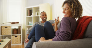 Black couple using electronic devices on sofa Royalty Free Stock Images
