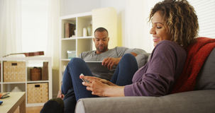 Black couple using electronic devices on sofa Stock Photo