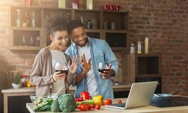 Black couple using laptop and greeting in kitchen Stock Images
