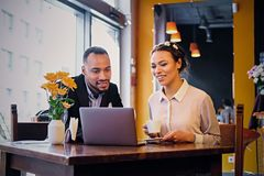 Free Black Couple Using Laptop In A Cafe. Stock Image - 116628281